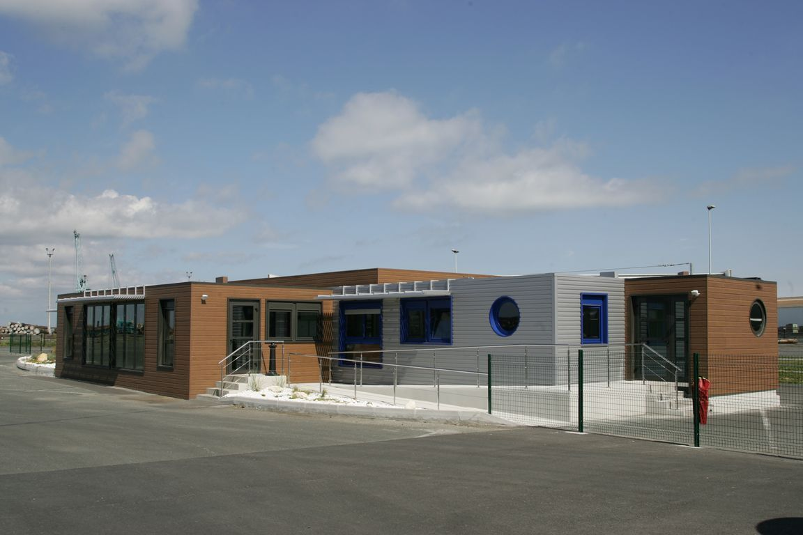 Bâtiment de bureaux construit à partir de modules, avec une façade architecturée qui se fond dans l'environnement.