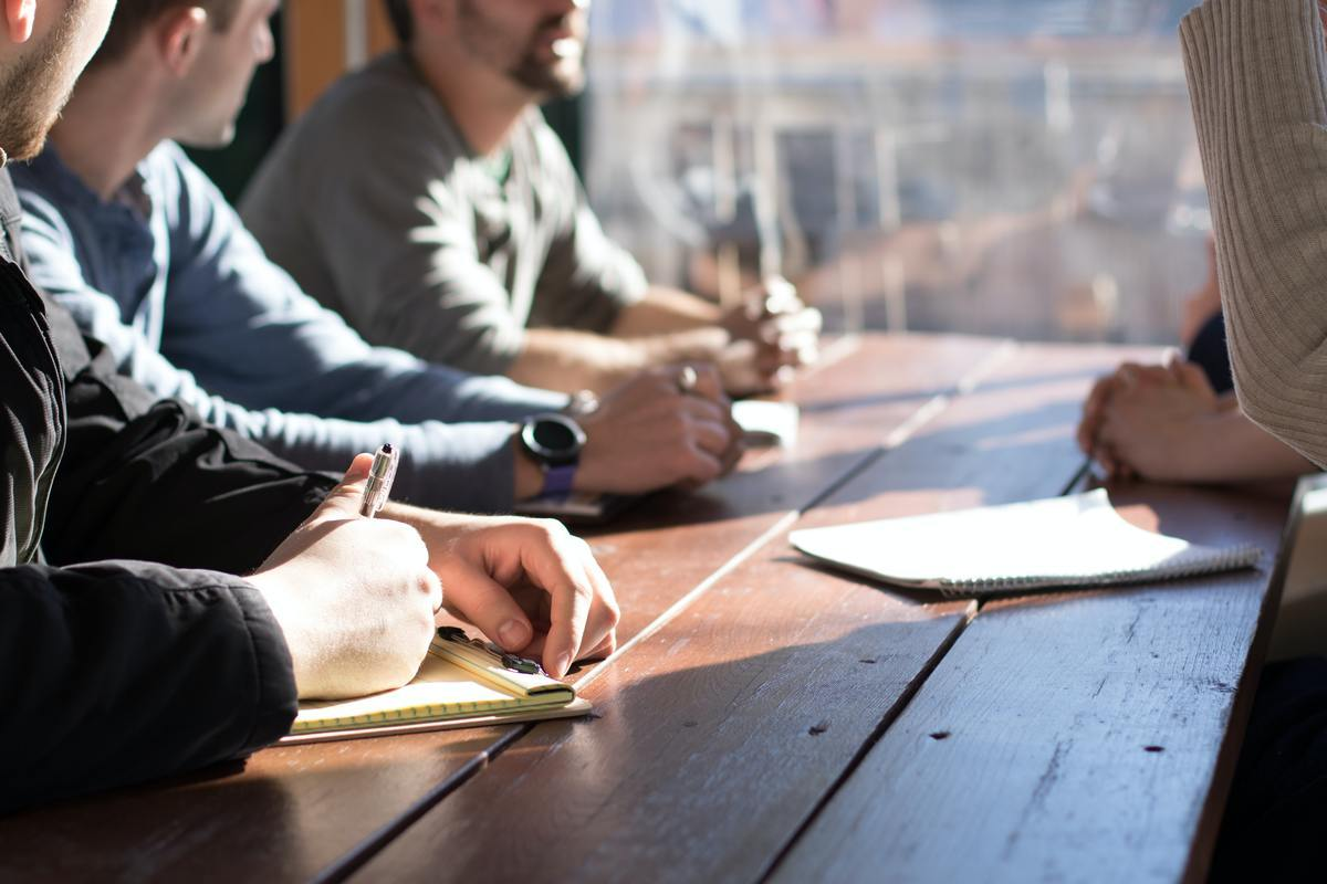 Quatres personnes en réunion qui se concerte autour d'un projet sur-mesure..