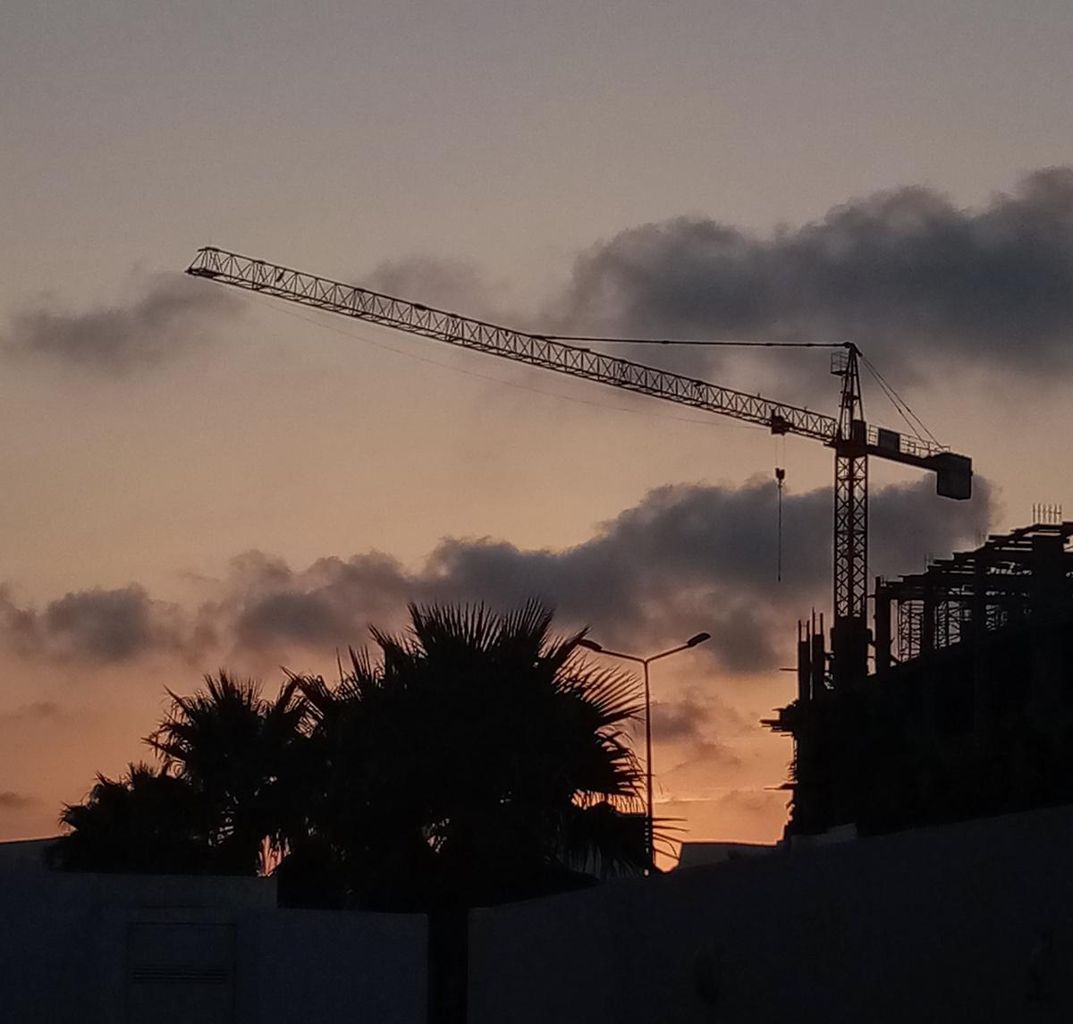Photo d'une grue de travaux au crépuscule.